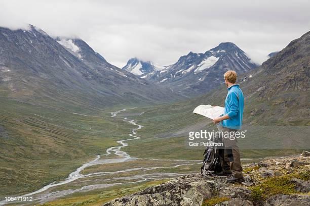 man with map in mountain surroundings - trondheim fotografías e imágenes de stock