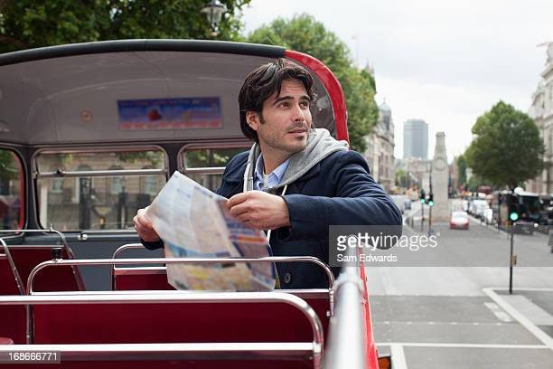 Man with map on double decker bus
