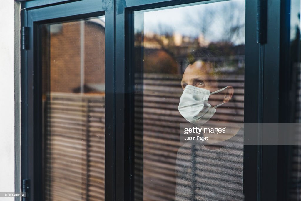 Man with mask looking out of window : ストックフォト