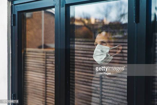 man with mask looking out of window - corona virus stock-fotos und bilder