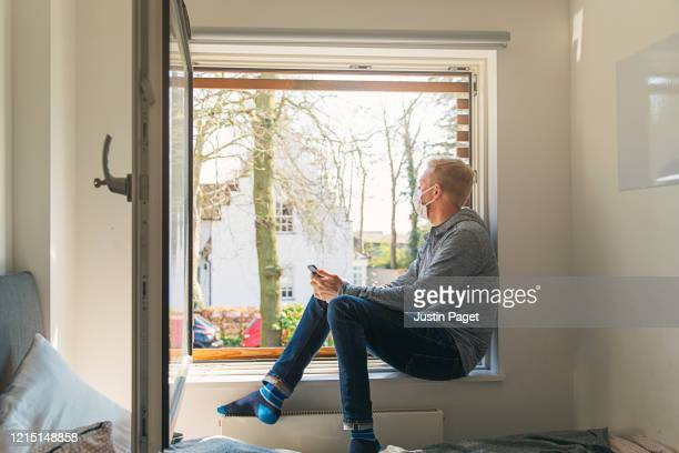 man with mask looking out of window - open stock pictures, royalty-free photos & images