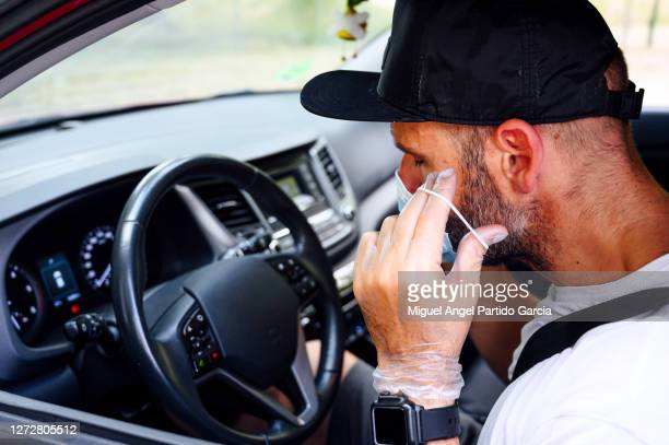 man with mask on car - stock photo. - travelstock44 stock pictures, royalty-free photos & images