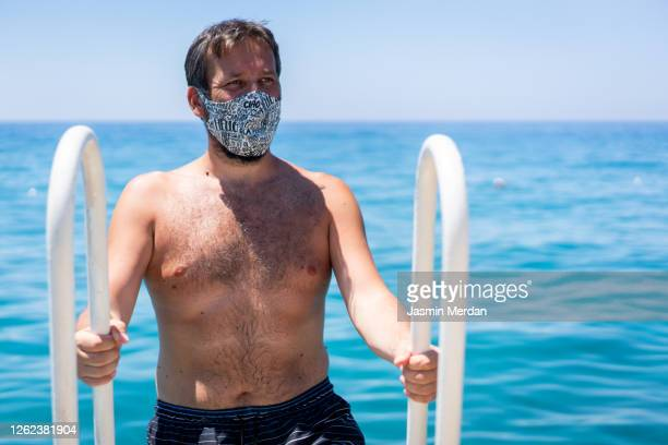man with mask on sea beach jetty - bronzage masque photos et images de collection