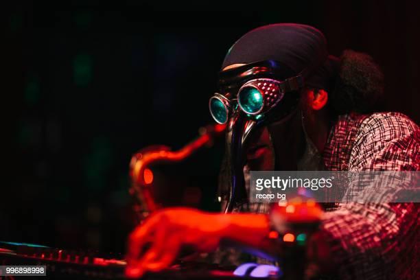 mann mit maske, die wiedergabe von musik auf der bühne - masked musicians stock-fotos und bilder