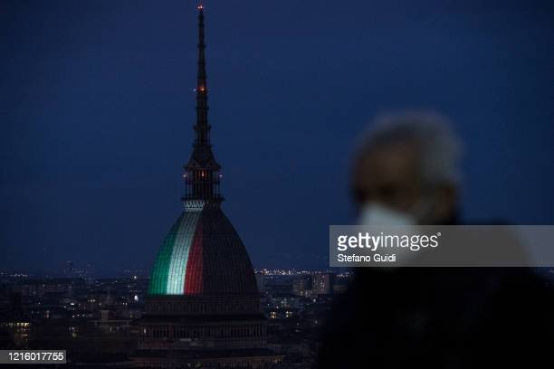 A man with mask walk by as the Mole Antonelliana is illuminated with the Italian flag to remember the many victims of the coronavirus pandemic on...