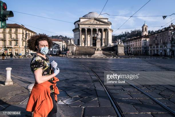 Man with mask walking in front of the Gran Madre Church in Turin as Italy continues its nationwide lockdown to control the coronavirus outbreak on...