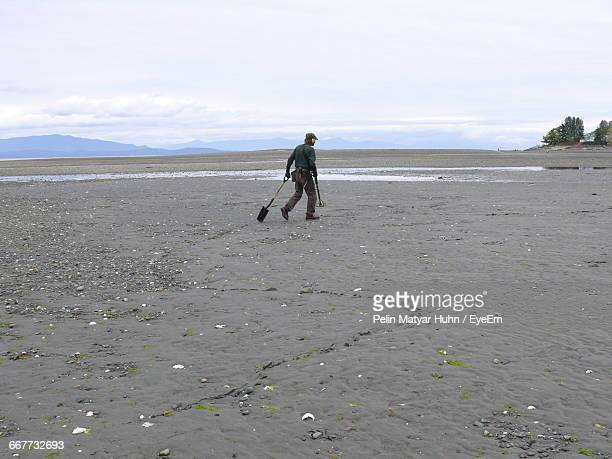 Man With Metal Detector And Shovel Walking On Sand At Beach