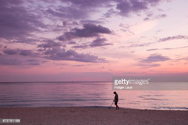 Man with metal detector on beach at sunset
