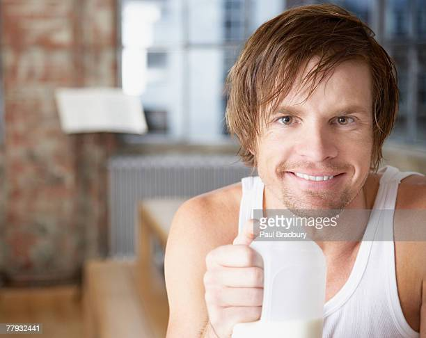 man with milk jug in modern home - milk carton stock photos and pictures