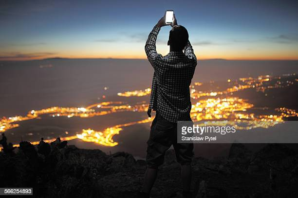 Man with mobile device at night city view