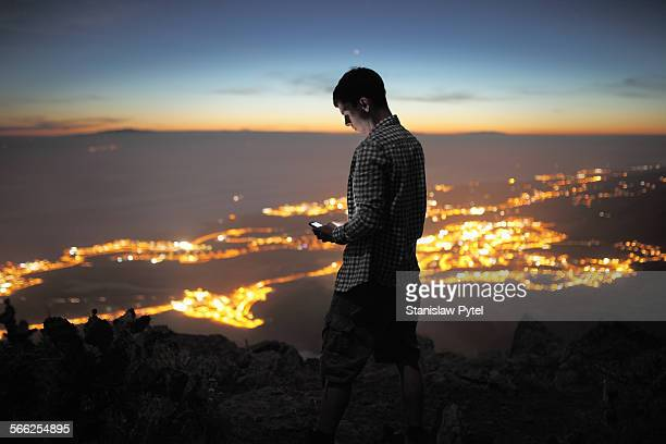 Man with mobile device at night, city view