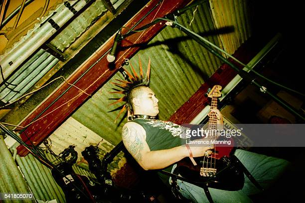 man with mohawk playing bass guitar - punk music stock pictures, royalty-free photos & images