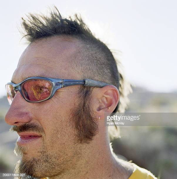 Man with mohawk wearing sunglasses, close-up of head