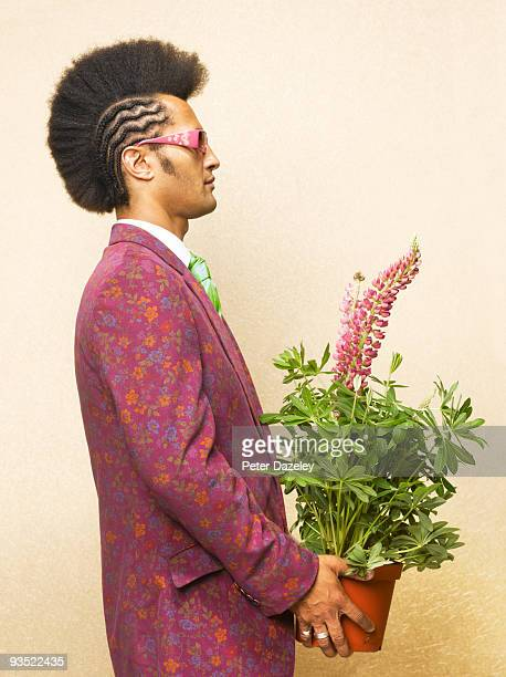 Man with Mohican haircut holding potted Lupin.