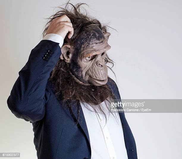 man with monkey mask against white background - monkey suit stock pictures, royalty-free photos & images