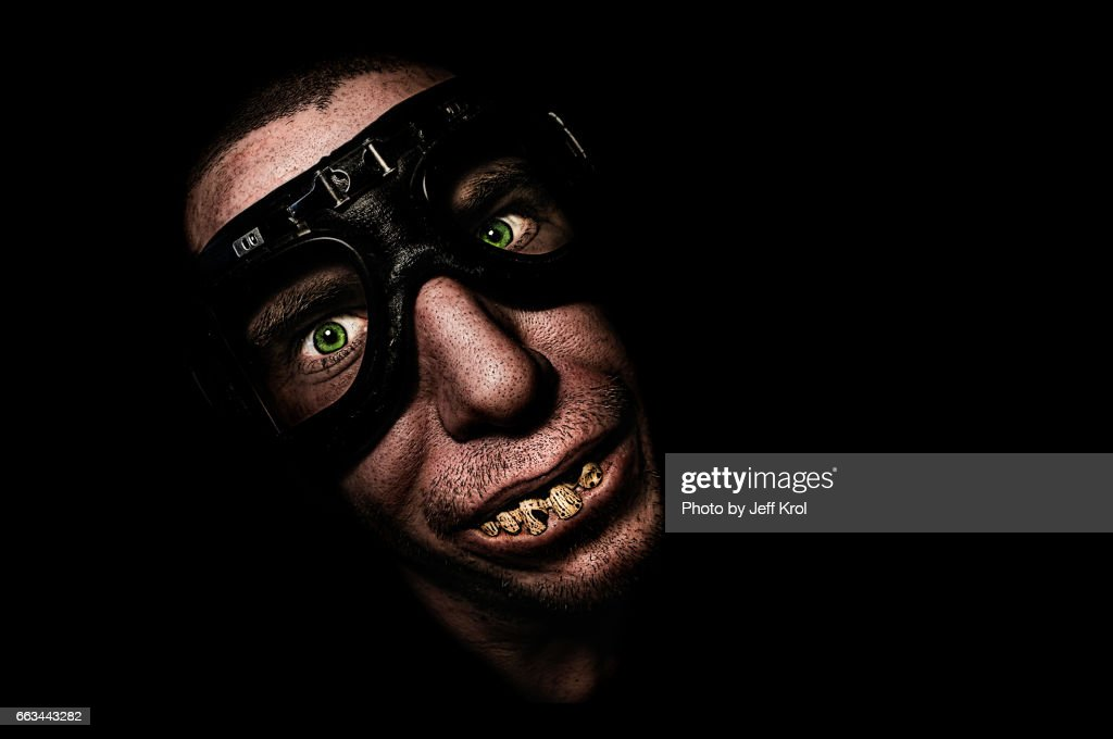 Man with motorcycle goggles or glasses, with funny fake teeth, smiling : Stock Photo