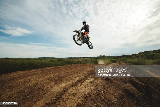 man with motorcycle jumping on landscape against sky - オートバイ競技 ストックフォトと画像