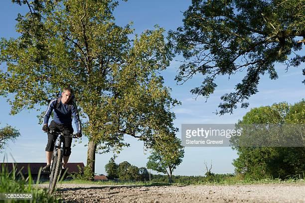 man with mountain bike under blue skies - stefanie grewel stock-fotos und bilder
