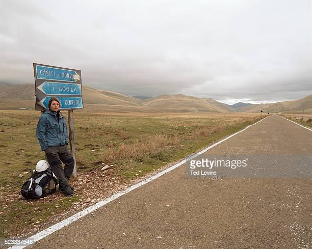 Man with Mountaineer Gear Leaning on Signpost Beside Road