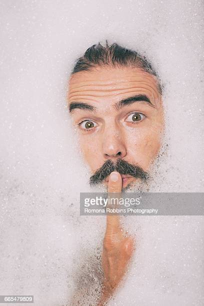 Man with moustache covered in bubbles finger on lips