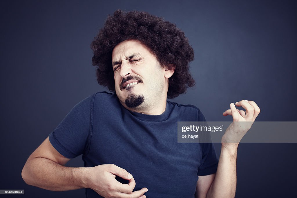 Man with moustache intensely plays air guitar : Stock Photo