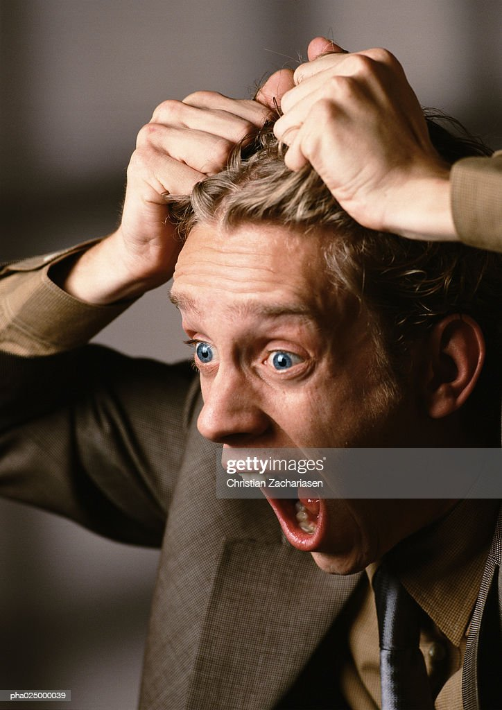Man with mouth and eyes wide open, pulling hair, close-up : Stockfoto