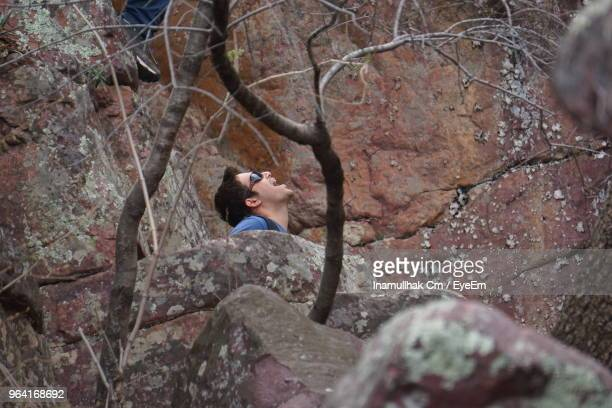 man with mouth open amidst rocks in forest - mid adult stock pictures, royalty-free photos & images