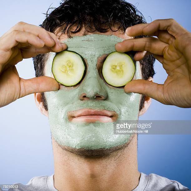 Man with mud mask and cucumber slices on eyes