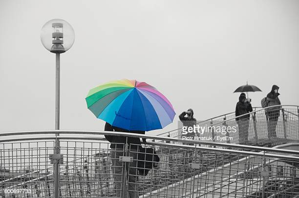 man with multi colored umbrella standing on bridge against clear sky - piotr hnatiuk photos et images de collection