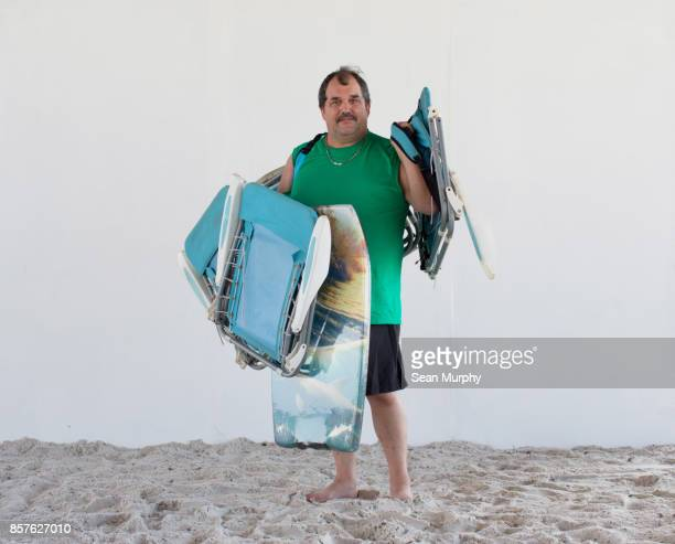 man with mustache holding beach chairs and boogie boards - destin beach stock pictures, royalty-free photos & images