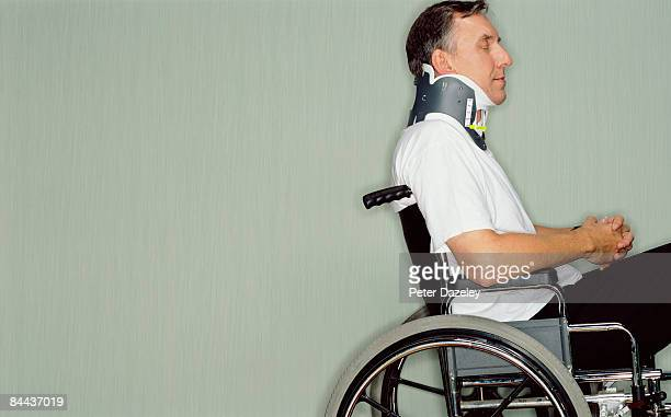 Man with neck brace in wheel chair in hospital.