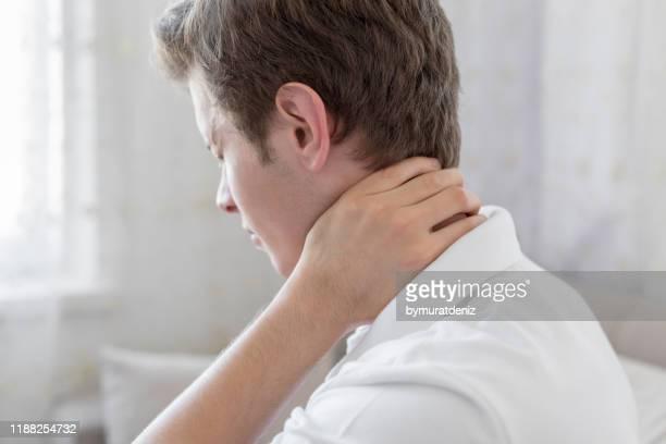 mann mit nackenschmerzen - hernie stock-fotos und bilder