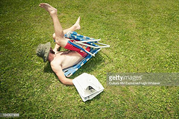 Man with newspaper falling off chair