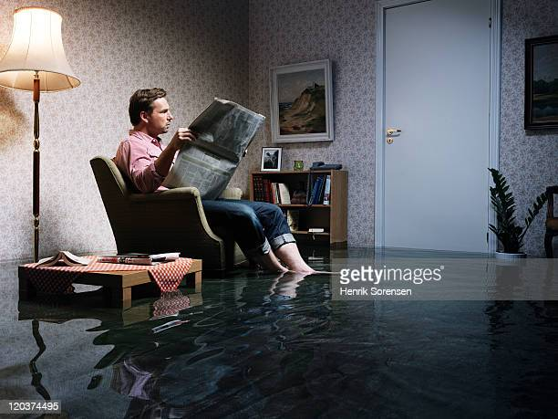 man with newspaper flooded room
