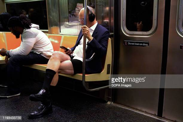 "Man with no pants rides in the subway while holding his cellphone. As a part of a comedic stunt in 2002 seven riders took their first ""No Pants..."
