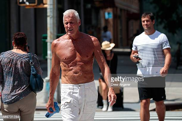 A man with no shirt on prepares crosses 23rd Street in the Chelsea neighborhood of Manhattan August 15 2016 in New York City The New York City area...