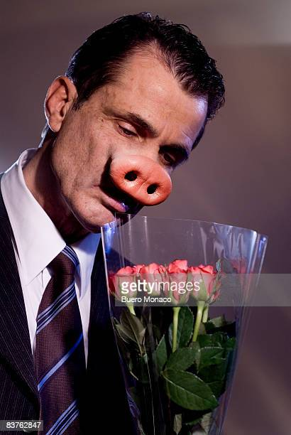 man with nose like a pig takes a smell at flowers - pig nose stock pictures, royalty-free photos & images