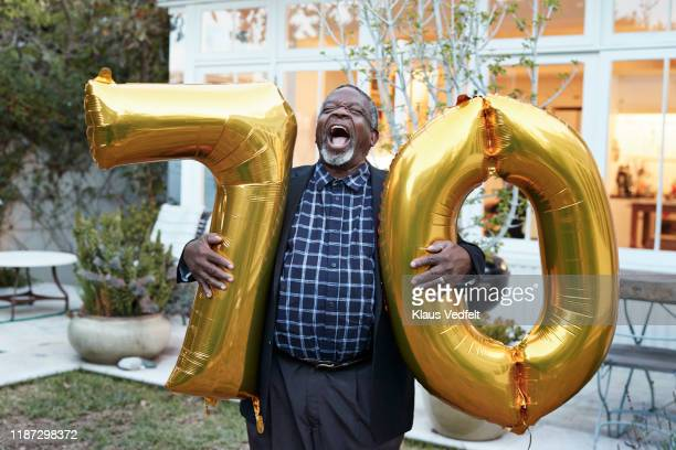 man with number 70 balloons laughing in backyard - wellness stock pictures, royalty-free photos & images