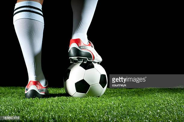 Man with one foot on a soccer ball