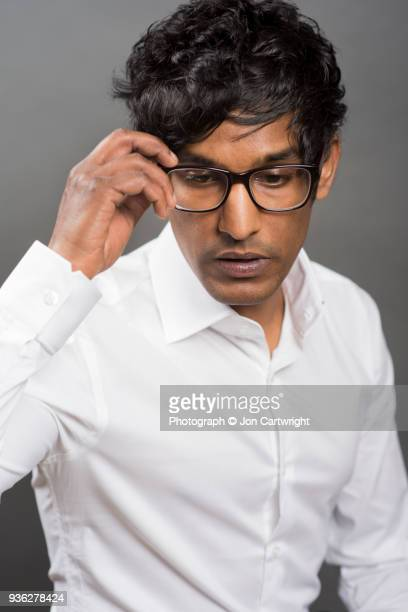 Man with one hand on his glasses looking down