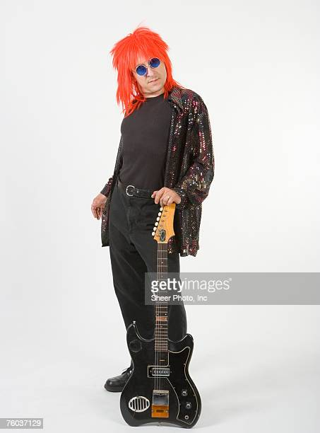 Man with orange hair holding electric guitar, portrait