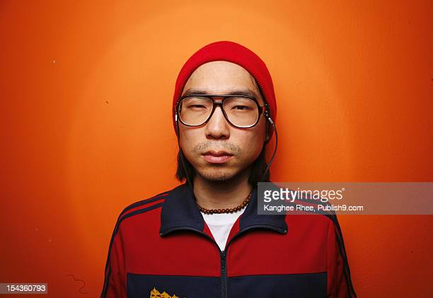 man with orange wall - korean ethnicity stock pictures, royalty-free photos & images