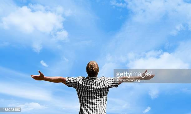 Mann mit ausgestreckten Armen Blick auf den Himmel