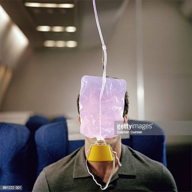 Man with oxygen mask hanging in front of face, on airliner