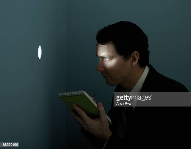 man with pad of paper spying through peep hole. - identity theft stock pictures, royalty-free photos & images