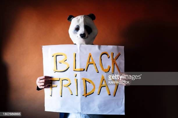 man with panda bear mask holding a black friday sign. - bear suit stock pictures, royalty-free photos & images