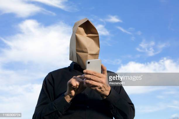 man with paper bag above his head using cell phone - instant messaging stock-fotos und bilder