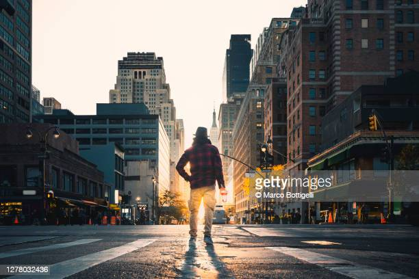man with paper coffee cup standing in the midst of the road, new york city - manhattan new york city stock pictures, royalty-free photos & images