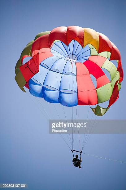 Man with parachute in air, low angle view