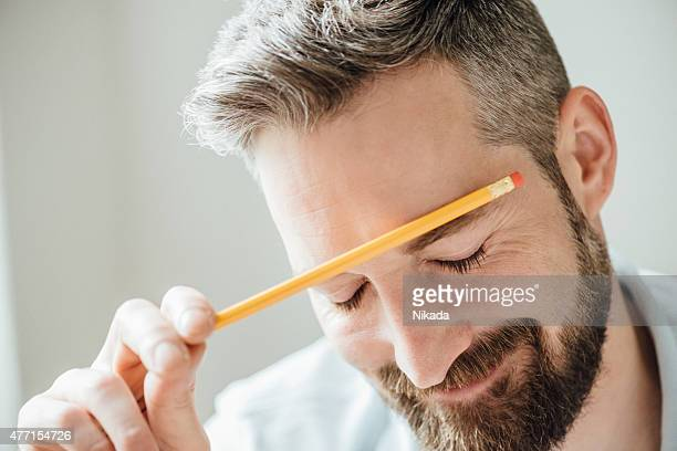 Man with pen studying at desk